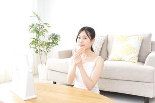 クリームを塗る女性の写真素材 [FYI04725029]