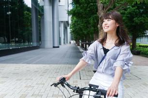 自転車に乗る若い女性の写真素材 [FYI04725223]