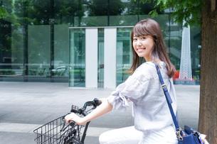 自転車に乗る若い女性の写真素材 [FYI04725224]