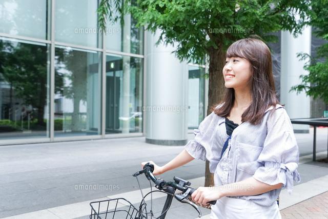 自転車に乗る若い女性の写真素材 [FYI04725225]
