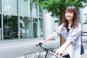 自転車に乗る若い女性の写真素材 [FYI04725226]