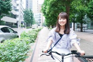 自転車に乗る若い女性の写真素材 [FYI04725228]