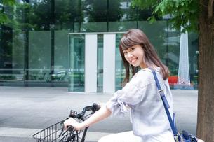 自転車に乗る若い女性の写真素材 [FYI04725230]