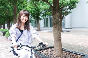 自転車に乗る若い女性の写真素材 [FYI04725232]