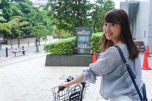 自転車に乗る若い女性の写真素材 [FYI04725236]