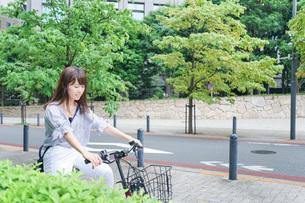 自転車に乗る若い女性の写真素材 [FYI04725244]