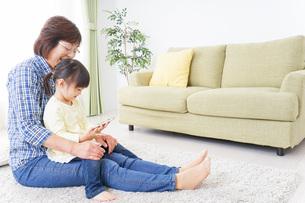 おばあちゃんとスマホを使う子供の写真素材 [FYI04725429]