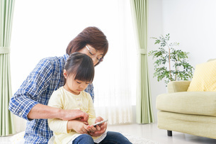 おばあちゃんとスマホを使う子供の写真素材 [FYI04725435]