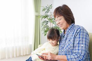 おばあちゃんとスマホを使う子供の写真素材 [FYI04725455]