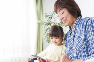 おばあちゃんとスマホを使う子供の写真素材 [FYI04725458]