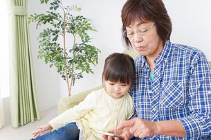 おばあちゃんとスマホを使う子供の写真素材 [FYI04725460]