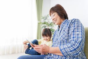 おばあちゃんとスマホを使う子供の写真素材 [FYI04725474]