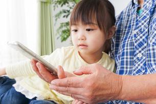 おばあちゃんとスマホを使う子供の写真素材 [FYI04725478]
