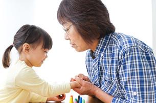おばあちゃんとゲームをする子供の写真素材 [FYI04725578]