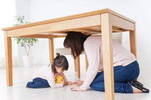 机の下に避難する親子の写真素材 [FYI04725917]