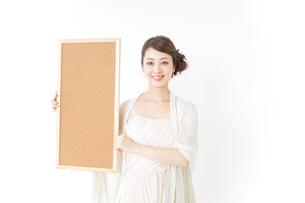 コルクボードを持つドレス姿の女性の写真素材 [FYI04726078]