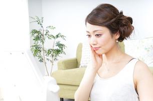 自宅でお化粧をする女性の写真素材 [FYI04726188]