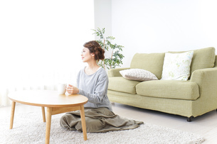 家でコーヒーを飲みくつろぐ女性の写真素材 [FYI04726194]