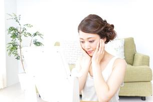 自宅でお化粧をする女性の写真素材 [FYI04726229]