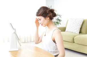 自宅でお化粧をする女性の写真素材 [FYI04726232]