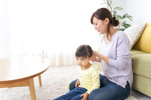 子どもの髪の毛を結ぶお母さんの写真素材 [FYI04726374]