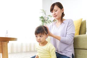 子どもの髪の毛を結ぶお母さんの写真素材 [FYI04726375]