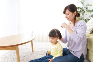 子どもの髪の毛を結ぶお母さんの写真素材 [FYI04726377]