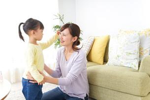 子どもの髪の毛を結ぶお母さんの写真素材 [FYI04726392]