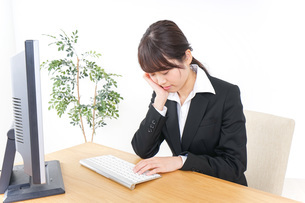 睡眠不足・居眠りをするビジネスウーマンの写真素材 [FYI04726633]
