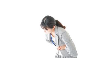 腹痛で苦しむ若いキャリアウーマンの写真素材 [FYI04726801]