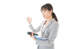 プレゼンテーション・司会をする若いビジネスウーマンの写真素材 [FYI04727036]