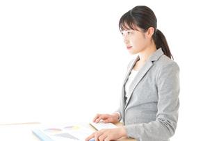 オフィスでデスクワークをする若いビジネスウーマンの写真素材 [FYI04727049]