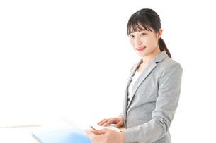 オフィスでデスクワークをする若いビジネスウーマンの写真素材 [FYI04727052]
