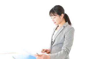 オフィスでデスクワークをする若いビジネスウーマンの写真素材 [FYI04727055]