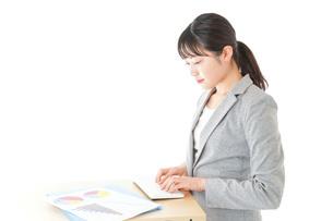オフィスでデスクワークをする若いビジネスウーマンの写真素材 [FYI04727056]
