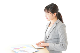 オフィスでデスクワークをする若いビジネスウーマンの写真素材 [FYI04727057]