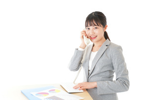 オフィスで固定電話を使う若いビジネスウーマンの写真素材 [FYI04727066]