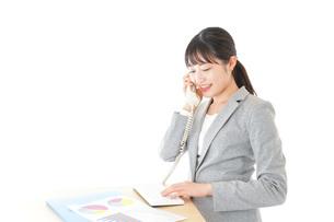 オフィスで固定電話を使う若いビジネスウーマンの写真素材 [FYI04727067]