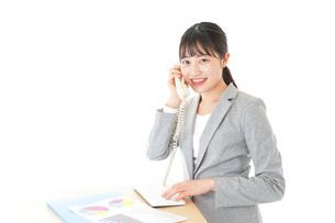 オフィスで固定電話を使う若いビジネスウーマンの写真素材 [FYI04727069]