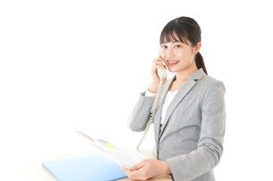 オフィスで固定電話を使う若いビジネスウーマンの写真素材 [FYI04727073]