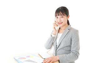 オフィスで固定電話を使う若いビジネスウーマンの写真素材 [FYI04727074]