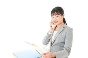 オフィスで固定電話を使う若いビジネスウーマンの写真素材 [FYI04727075]