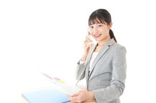 オフィスで固定電話を使う若いビジネスウーマンの写真素材 [FYI04727076]