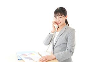 オフィスで固定電話を使う若いビジネスウーマンの写真素材 [FYI04727078]
