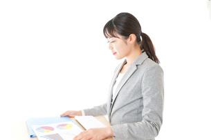 オフィスでデスクワークをする若いビジネスウーマンの写真素材 [FYI04727087]