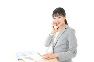 オフィスで固定電話を使う若いビジネスウーマンの写真素材 [FYI04727091]