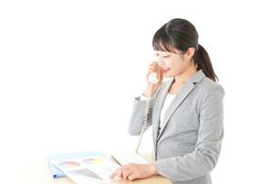 オフィスで固定電話を使う若いビジネスウーマンの写真素材 [FYI04727092]