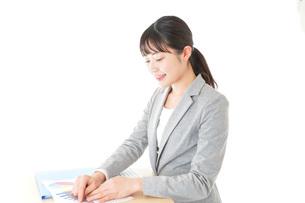 オフィスでデスクワークをする若いビジネスウーマンの写真素材 [FYI04727095]