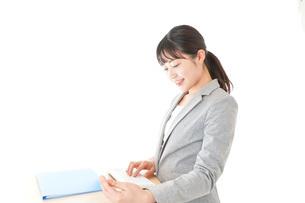 オフィスでデスクワークをする若いビジネスウーマンの写真素材 [FYI04727107]