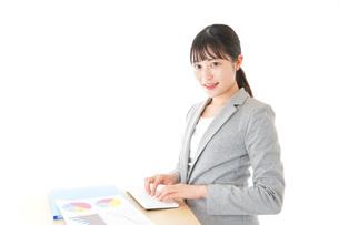 オフィスでデスクワークをする若いビジネスウーマンの写真素材 [FYI04727112]